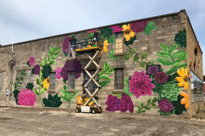 Upper Iowa University art student Jordyn Brennan puts the final touches an a large mural on the south side of the Fire Farm building. Her work has caught the attention of Elkader residents and visitors, many of who stopped to chat with her during the weeks-long project.